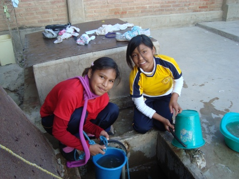 Two of the middle school aged girls are taking water out of the well to wash their clothes.
